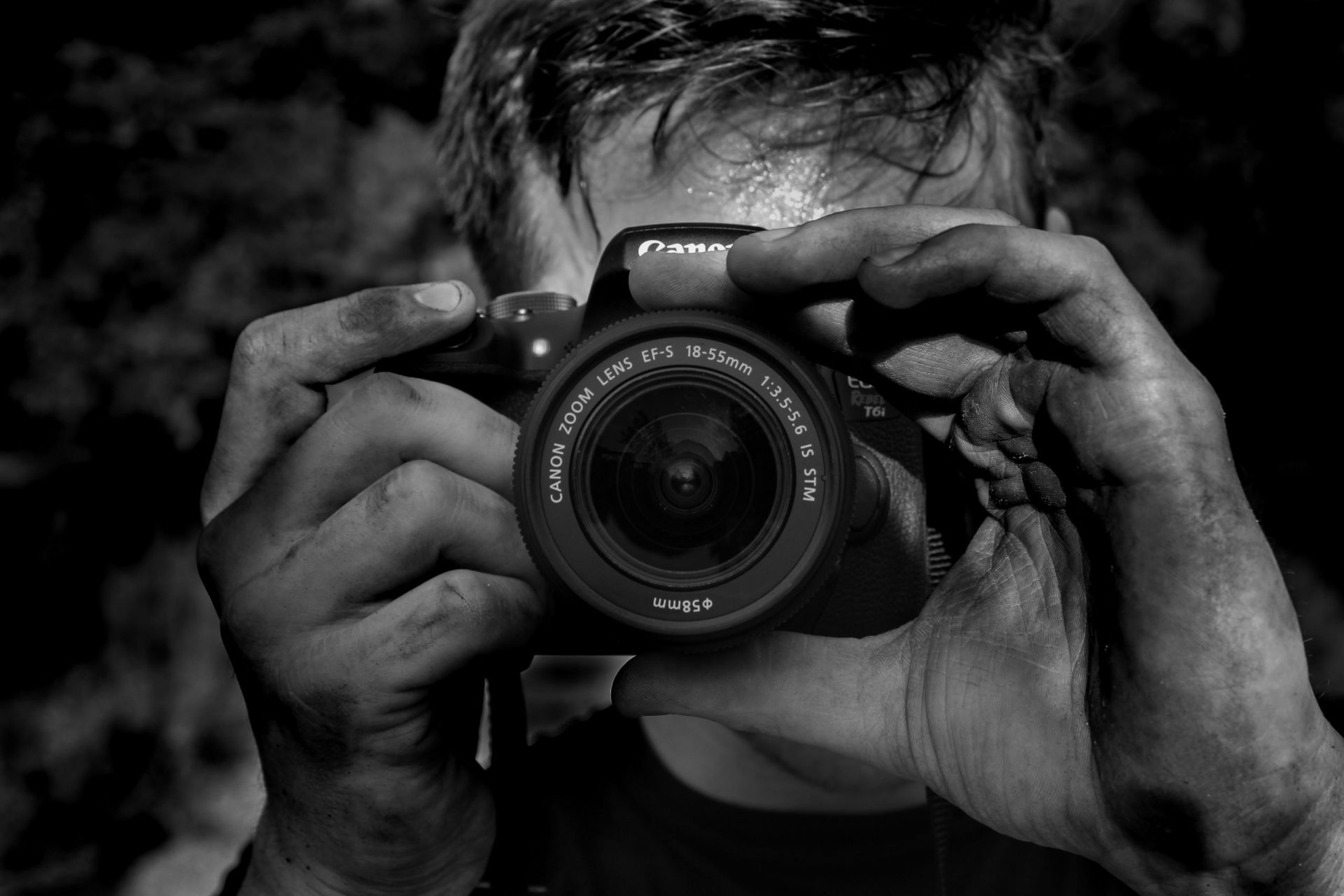 10 Common Travel Photography Mistakes and How to Avoid Them - Man taking a picture with a camera in black and white
