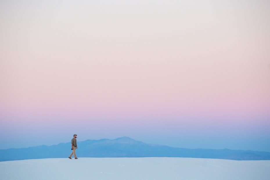 10 Travel Photography Tips - How to Take Great Pictures While Traveling - man hiking on dunes