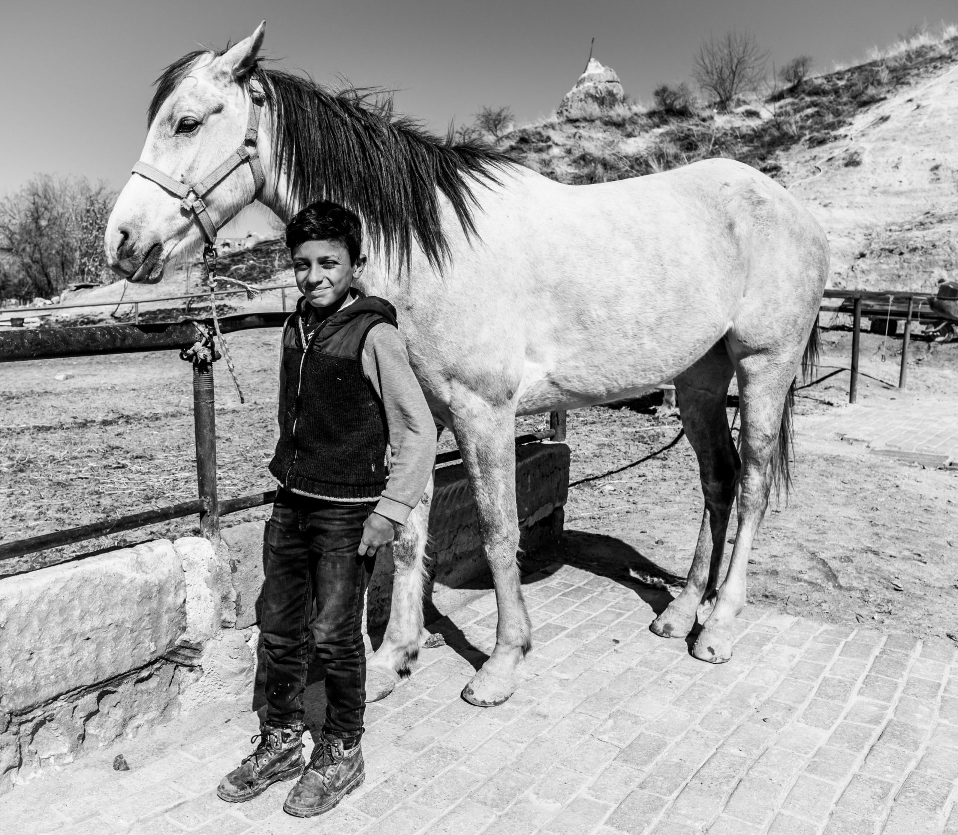 10 Travel Photography Tips - ask locals - portrait of Anatolian Turkish boy posing with horse in Cappadocia