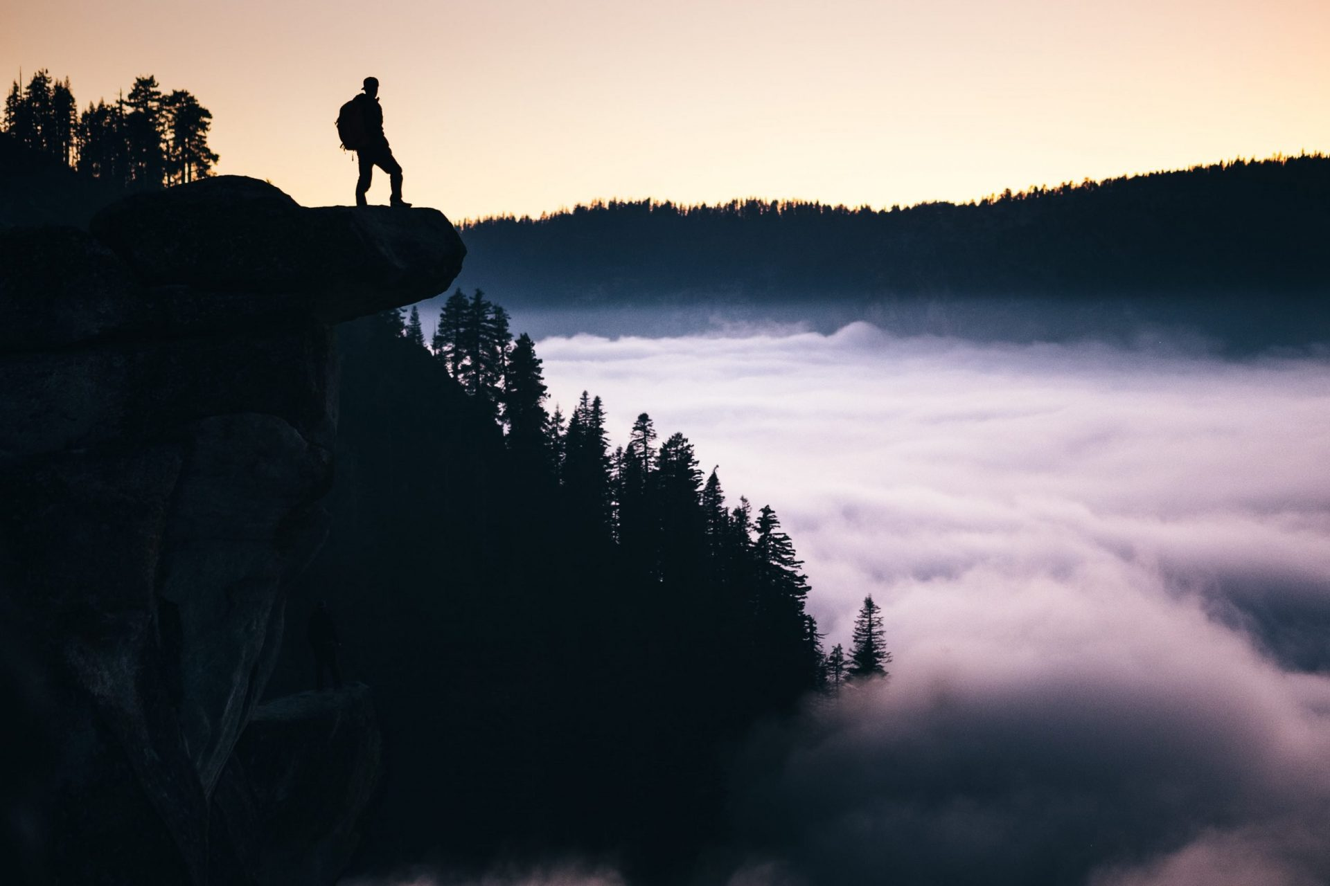 A Step-by-Step Guide on How to Become a Digital Nomad - man stunding on mountain in Yosemite at sunrise