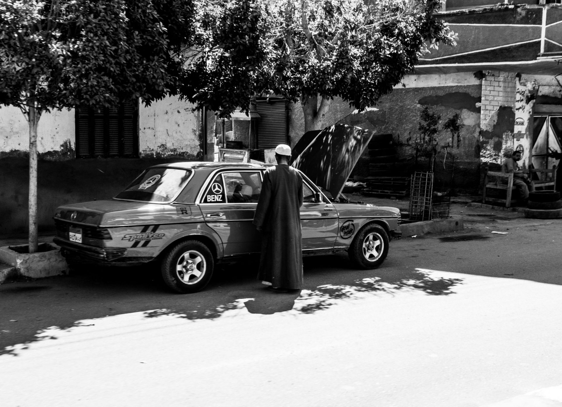 Man standing next to old Mercedes with open car in Edfu, Egypt