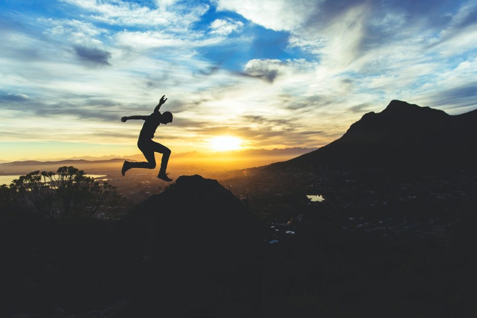 Should You Become a Digital Nomad? 6 Good and Bad Reasons - Man jumping on a mountain at sunset