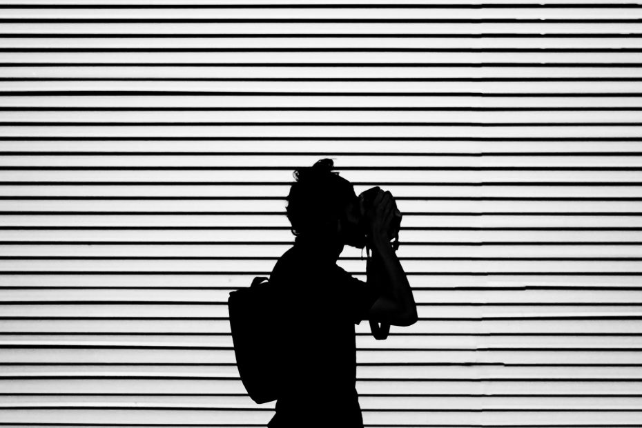 The Best Mirrorless Cameras for Travel Photography - black and white shot of girl with camera