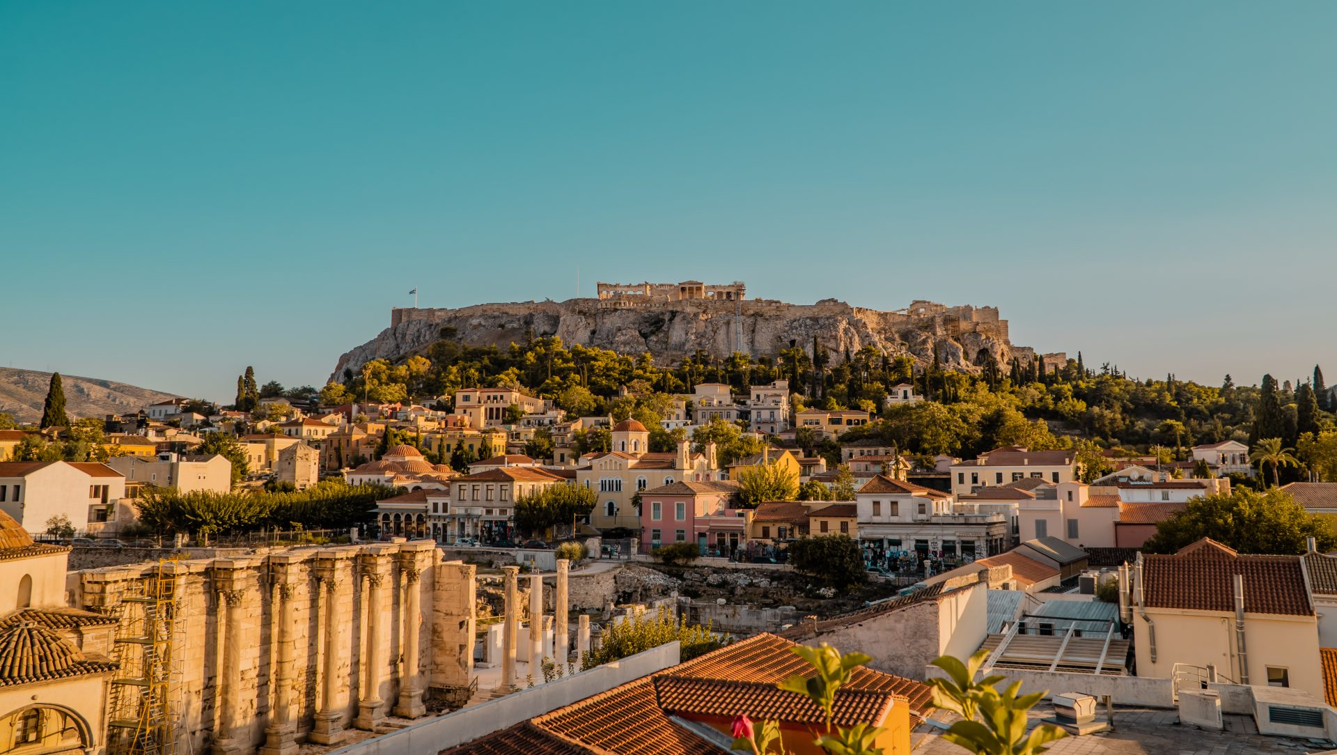 Athens, Greece - September 30, 2020 - beautiful aerial panoramic sunset view of central Athens rooftops with Acropolis, Tzisdarakis Mosque, and Hadrian's Library