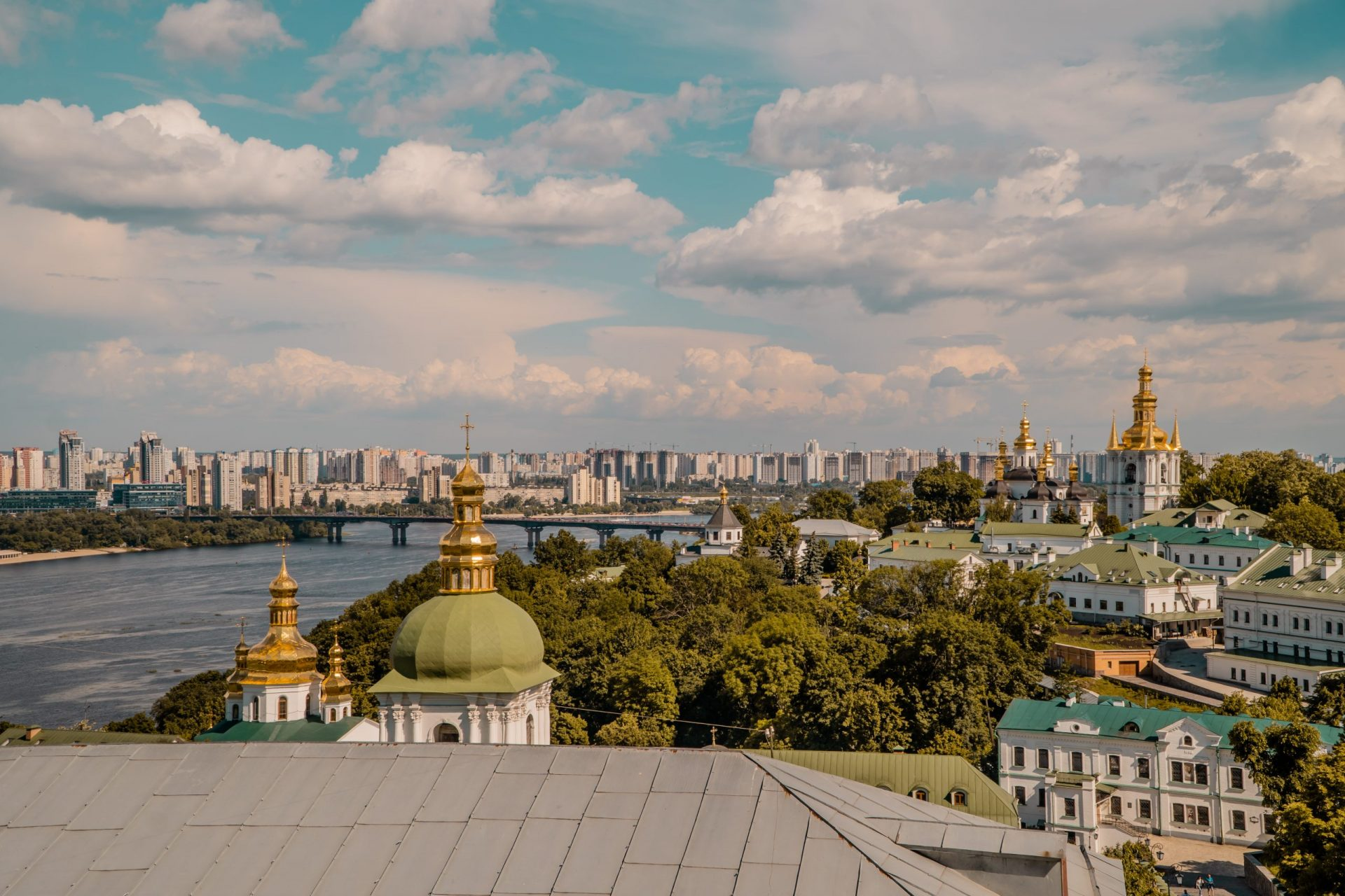 Things to do in Kyiv - panoramic sunset view of gold-domed churches, Dnipro river, and communist housing blocks seen from Pechersk Lavra (Caves)