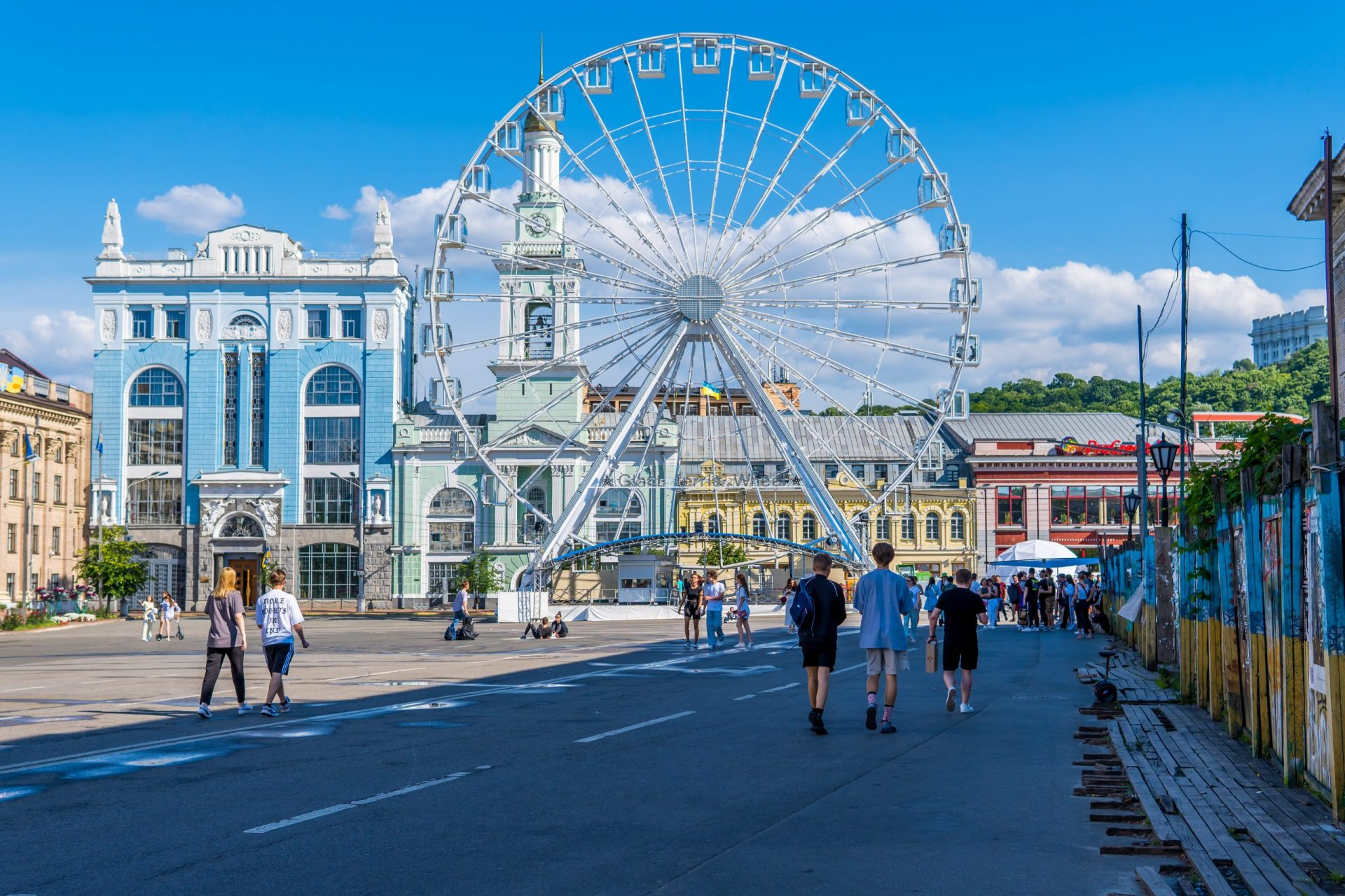 Things to do in Kyiv - people on the main square of the Podil neighborhood with ferris wheel and traditional architecture