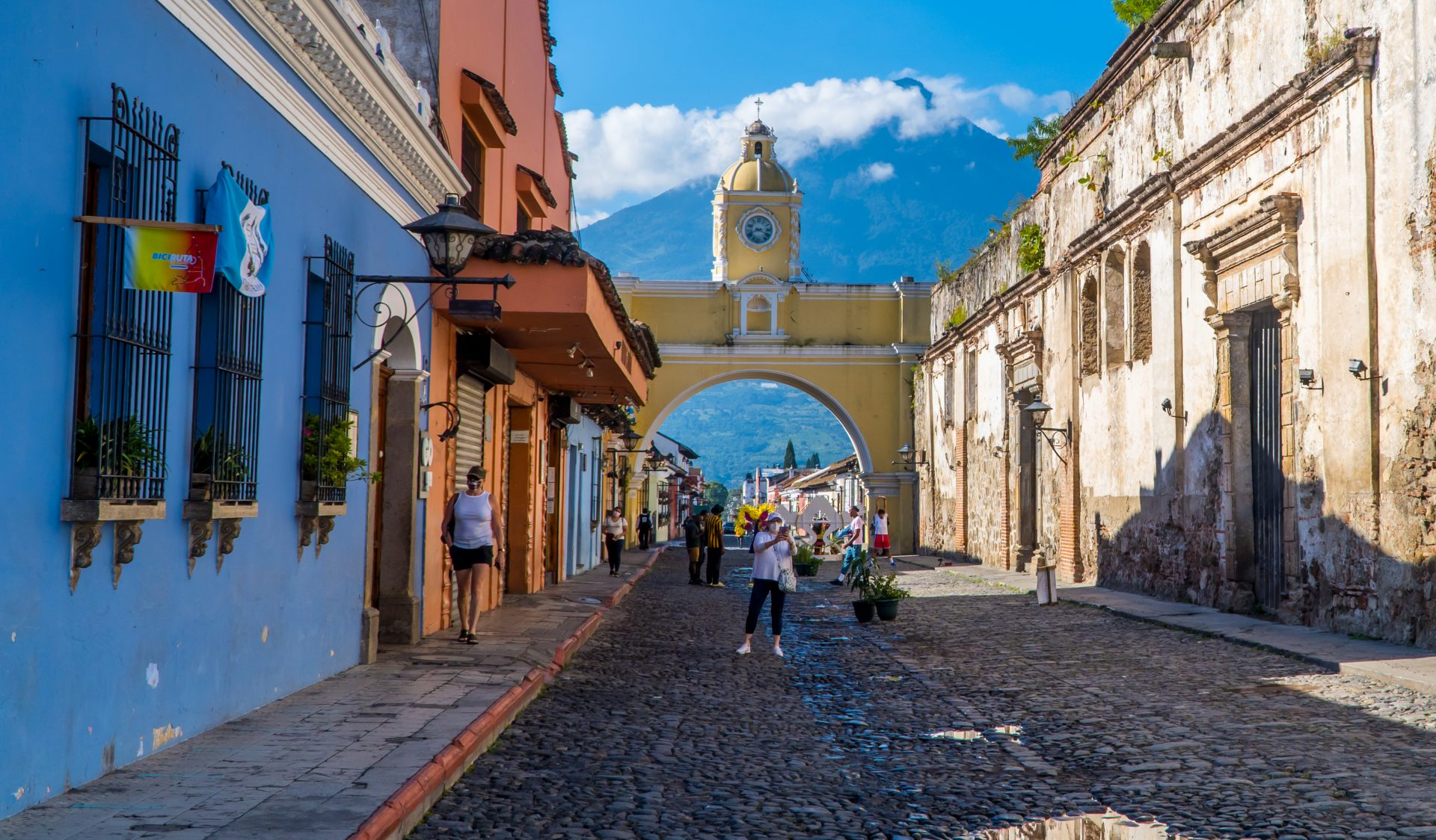 Things to do in Antigua Guateamal - Street photography of tourists at Santa Catalina Arch
