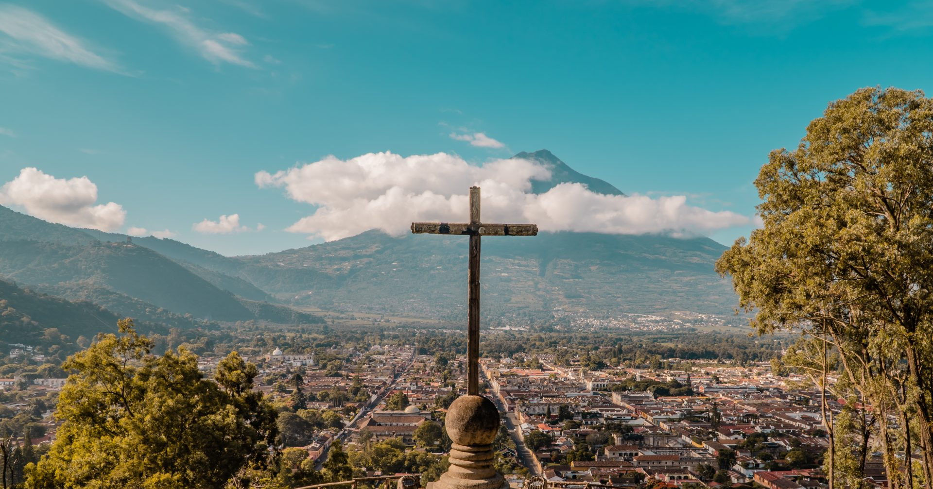 Things to do in Antigua Guatemala - featured - sunrise view of the city of Antigua, Guatemala with Agua Volcano from Cerro de la Cruz Viewpoint